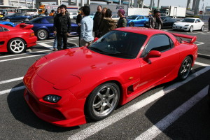Front left picture of a red Mazda RX-7 at Daikoku Futo