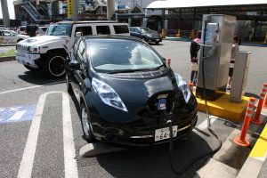 Picture of a Nissan Leaf recharging at Daikoku Futo with a Hummer H2 passing in the background